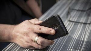 Miehellä kädessä älypuhelin.