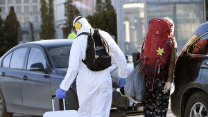 Suojapukuun pukeutunut mies ja matkalta palannut nainen Helsinki-Vantaan lentoasemalla.