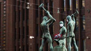 Kolmen sepän patsas hengityssuojilla 31.3.2020