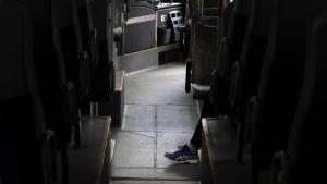 Matkustajan jalat tyhjällä bussin käytävällä.