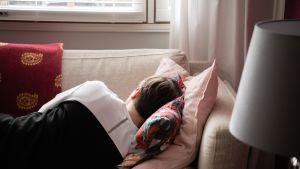 Nainen päiväunilla sohvalla.