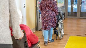 Työntekijät työntävät vanhuksia pyörätuolissa vanhustenkeskuksessa.