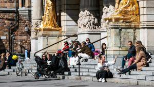 Ihmisjoukko istuu kuninkaallisen draamateatterin portailla Tukholmassa.