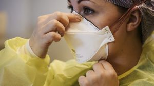 Kuvassa on hegityssuojaa käyttävä sairaanhoitaja.