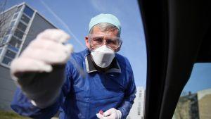Saksalaislääkäri ottamassa koronatestiä drive-in -testausasemalla Hallessa 27. maaliskuuta.