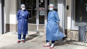 Sairaanhoitajia suojavaatteissa koronavastaanoton ulko-ovella Oulussa.