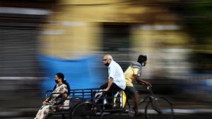 Hengityssuojaimiin pukeutunut mies ja nainen istuvat tavarapyörän kyydissä Kalkutassa.