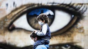 Kasvomaskeihin pukeutuneet mies ja lapsi Roomassa.