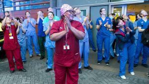 Sairaalan edessä terveydenhoitohenkilökuntaa taputtamassa.