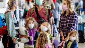 Kuvassa kolme aikuista ja neljä lasta. Kuva on otettu Schipholin lentokentällä Hollannissa.