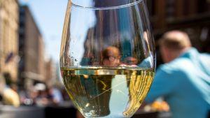 Viinilasi edustalla ja ihmisiä taustalla terassilla