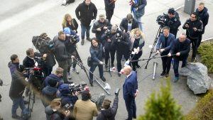 Holdenin edessä puoliympyrässä median edustajia. Kuva otettu ylhäältä alas kadulle päin.