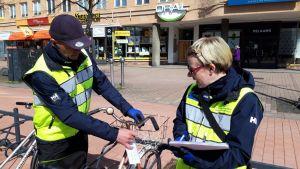 Kari Pesonen ja Maarit Hyttinen laittavat siirtokehotuksia Joensuun keskustaan hylättyihin polkupyöriin.