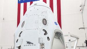 Valkoinen avaruuskapseli hallissa. Seinällä on suuri Yhdysvaltain lippu.