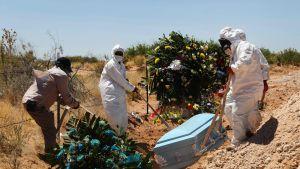 Kuvassa haudataan koronavirukseen kuollutta ihmistä.