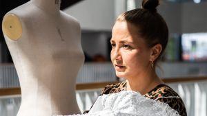 Vaatetussuunnittelua opiskeleva Sofia Ilmonen mallailee asua mallinuken päälle.