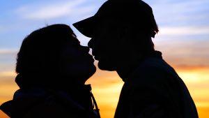 Pariskunta suutelee kesäyössä.