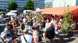Ihmisiä juhannusaattoaamun torikahveilla Hakaniemen torilla Helsingissä.