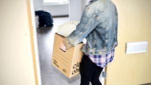 Henkilö kantaa muuttolaatikkoa asuntoon.