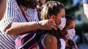 Äiti asettelee maskia lapsen kasvoille