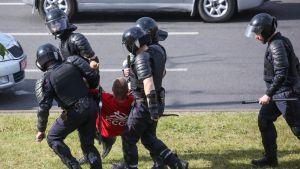 Mellakkavarusteiset poliisit kantavat miestä kadulla
