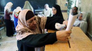 Nainen pudottaa äänestyslippuaan puulaatikkoon.