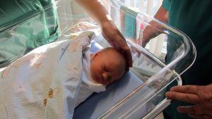Vastasyntynyt vauva sairaalassa hoitohenkilökunnan ympäröimänä.