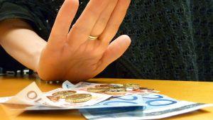 Nainen laittamassa kättä rahojen päälle.