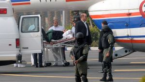 Egyptin entinen presidentti siirretään paareilla helikopterista ambulanssiin.