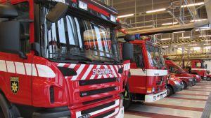 Kuvassa paloautoja ja muuta pelastuskalustoa paloasemalla
