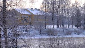 Keltainen koulurakennus näkyy etäällä talvisten koivujen ja joenuoman takana.