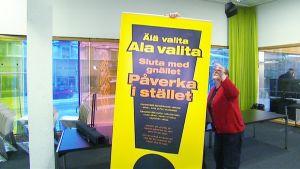 Vaalivirkailijat kiinnittävät julistetta, jossa lukee 'Älä valita, ala valita'.