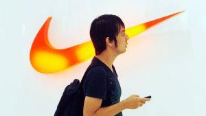 Indonesialainen mies kävelee Niken valaistun logon ohi kauppakeskuksessa.