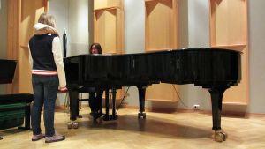 Iida Jokelainen koelaulussa - kuoronjohtaja Mari Kesäniemi säestää pianolla.