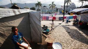 Lapsia telttakylässä, taustalla taloja ja palmuja.