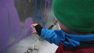 Lapsi maalaa graffitiseinälle.