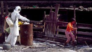 Suojapukuun ja naamariin pukeutun viranomainen levittää desinfioivaa jauhetta slummissa. Asukas kiirehtii pois jauhesuihkun alta.