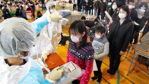 Ihmisiä jonossa, etummaisena lapsi, josta valkopukuinen hoitaja tai lääkäri mittaa säteilyarvoja laitteella.
