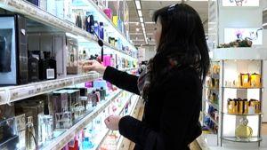 Nainen ostoksilla tavaratalon hajuvesiosastolla.