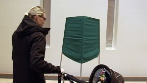 Nainen lähestyy lastenvaunujen kanssa äänestyskoppia