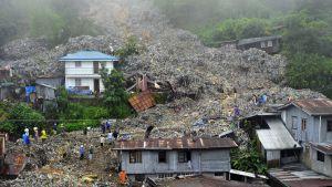 """Baguion kaatopaikalta liikkelle lähtenyt """"jätevyöry"""" vahingoitti lähiseudun rakennuksia pahoin ja hautasi myös ihmisiä alleen."""