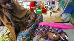 Somaliäiti kahden aliravitun lapsensa kanssa.