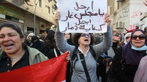 Nainen kannattelee protestikylttiä mielenosoituksessa Kairon parlamentin ulkopuolella. Ympärillä on paljon naispuoleisia mielenosoittajia.