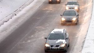 Autoja jonossa lumisella moottoritiellä.