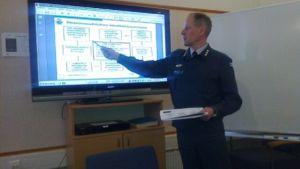 Eversti Jukka Ahlberg viittoo tietokone-esitystä ison näytön edessä.