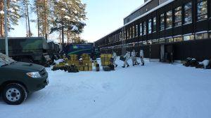 Varusmiehet kantavat varustelaatikoita Pioneerirykmentin pihalla Keuruulla.