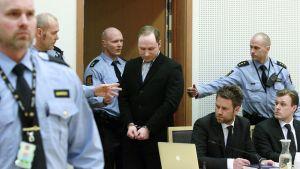 Breivikiä tuodaan oikeussaliin poliisien ympäröimänä.