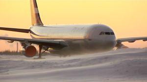 Finnairin lentokone laskeutuu auringonnousun aikaan.