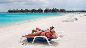 Turisteja hiekkarannalla Malediiveilla.