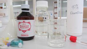 Kuvassa ruusuvettä, glyserolia ja etanolia laboratoriossa, jossa valmistetaan itsetehtyä partavettä